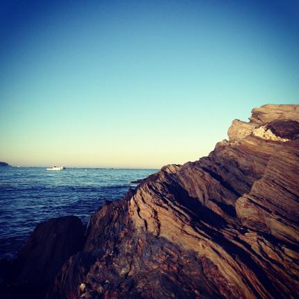 Rocks Overlooking Sailboat on the Ocean