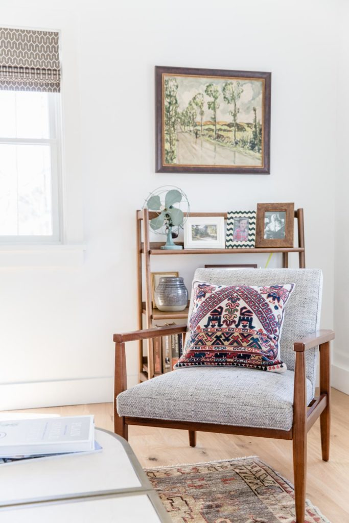 A Cozy Living Room Corner Features A Chair And Coffee Table From Youngs. A  Shelf Set Is Filled With Family Photos And A Vintage Fan.