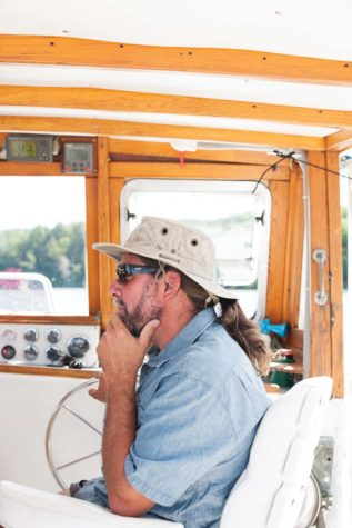 Matt St. Cyr sits at the helm of his boat, the Bellatrix.