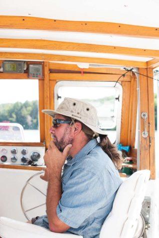 Matt St. Cyr sits at the helm of his boat, the Bellatrix.