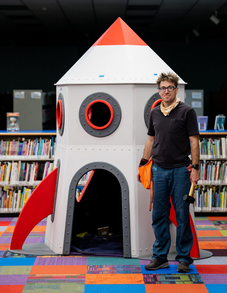 Rusty Lamar standing next to his rocket reading nook.
