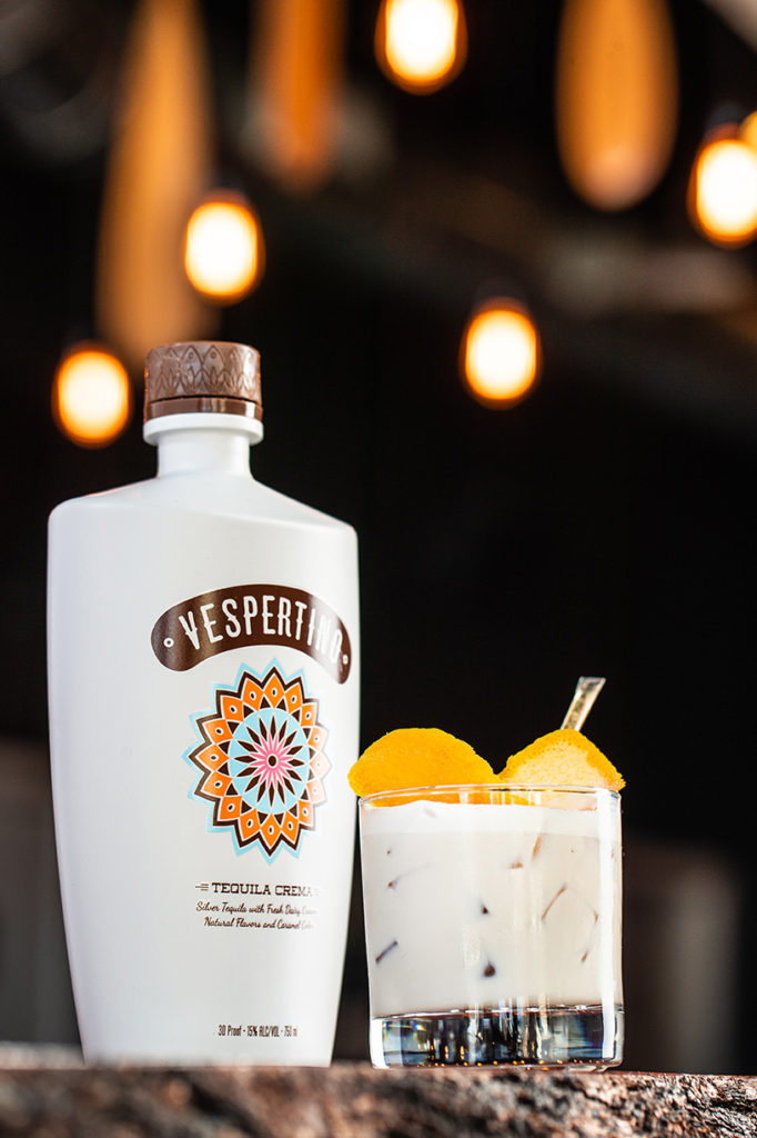 A bottle of Vespertino sits next to a Milk & Honey cocktail