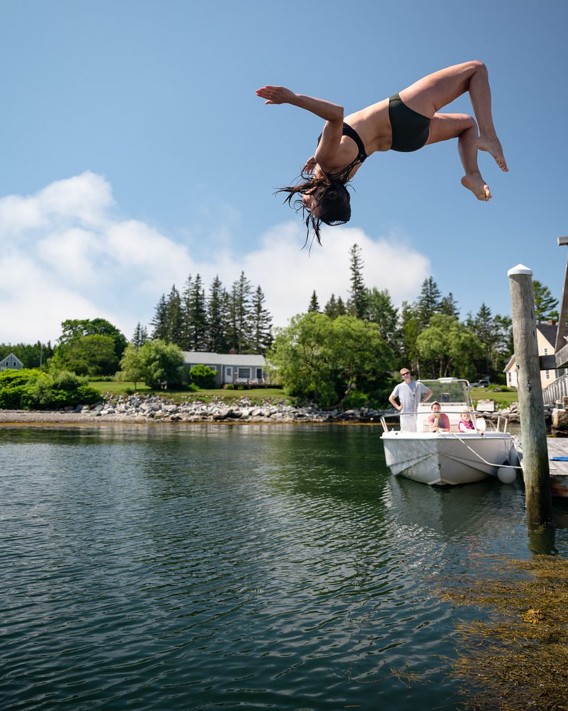 The photographer's wife shows off for the kids, jumping into Tenants harbor, Maine.