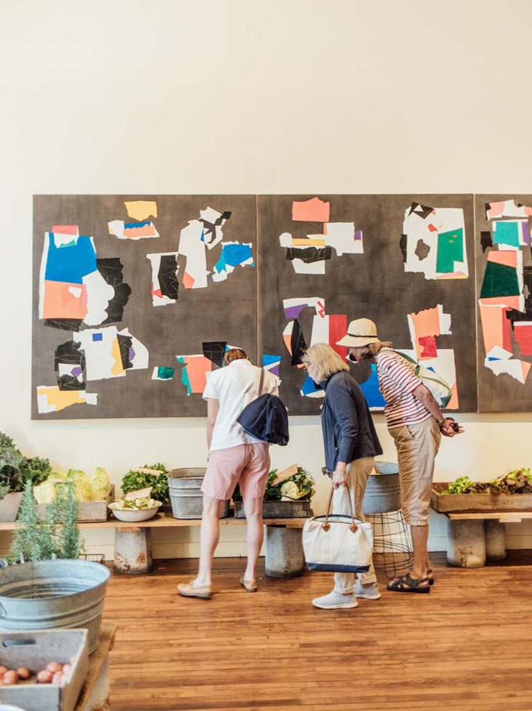 Chase's Daily customers survey the farm stand plants and Margaret Nomentana's artwork on display in the Perimeter Gallery.