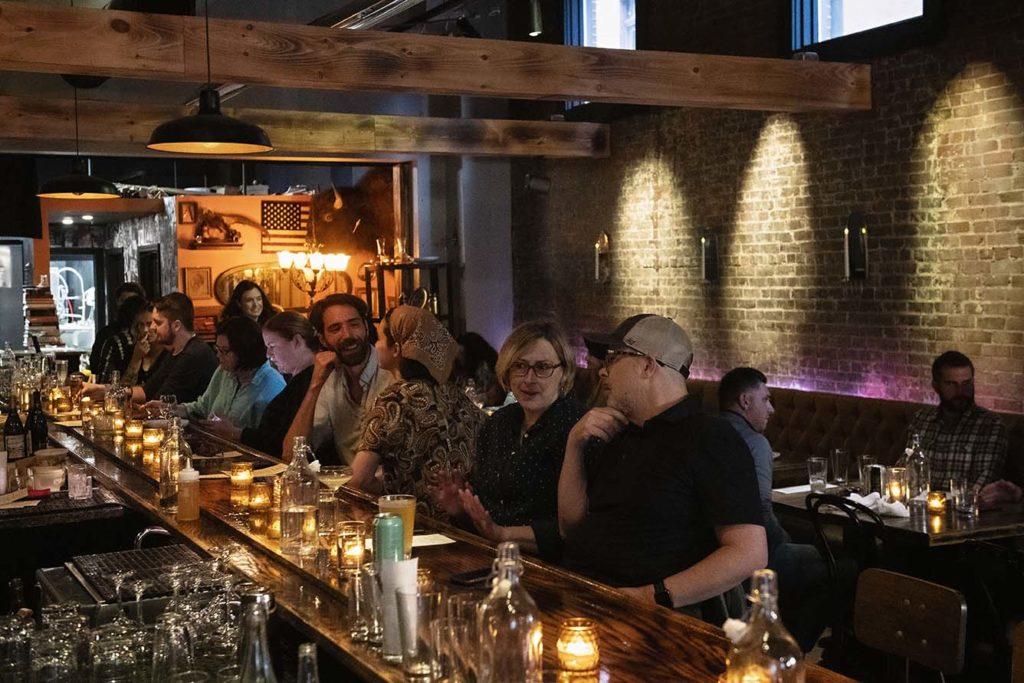 Diners line the long bar inside Broken Arrow's warm, moody space.