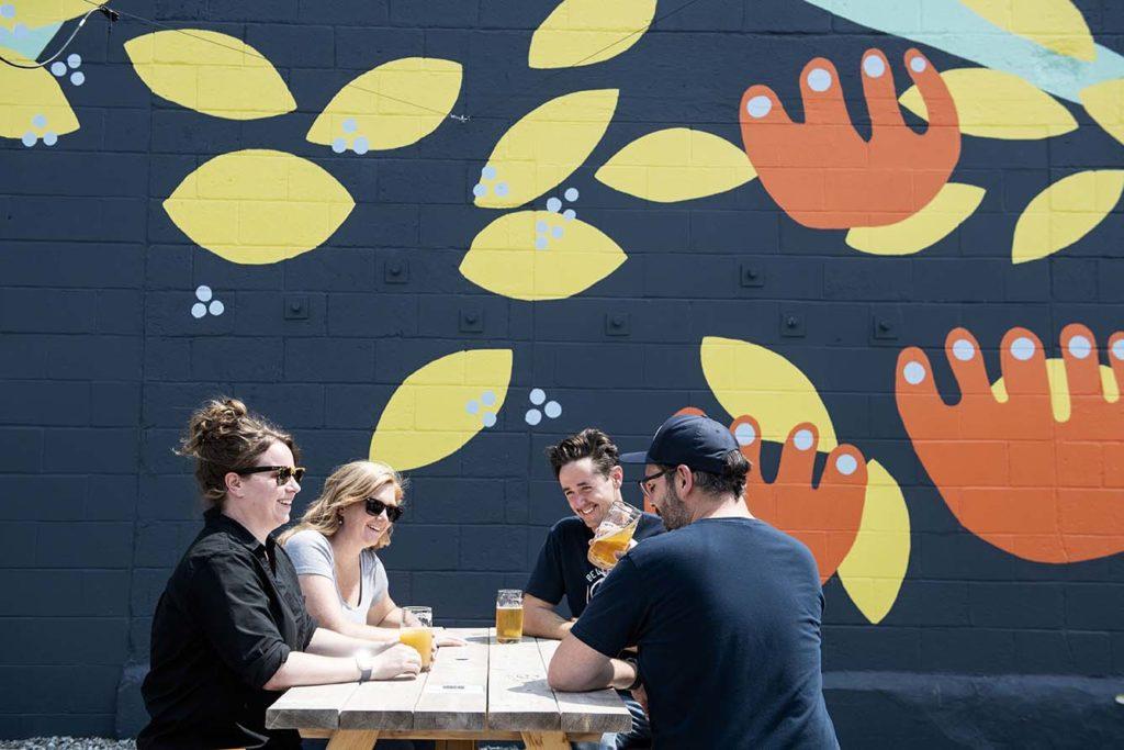 Belleflower Brewery owners enjoy pints of beer in the urban beer garden beneath a whimsical mural.
