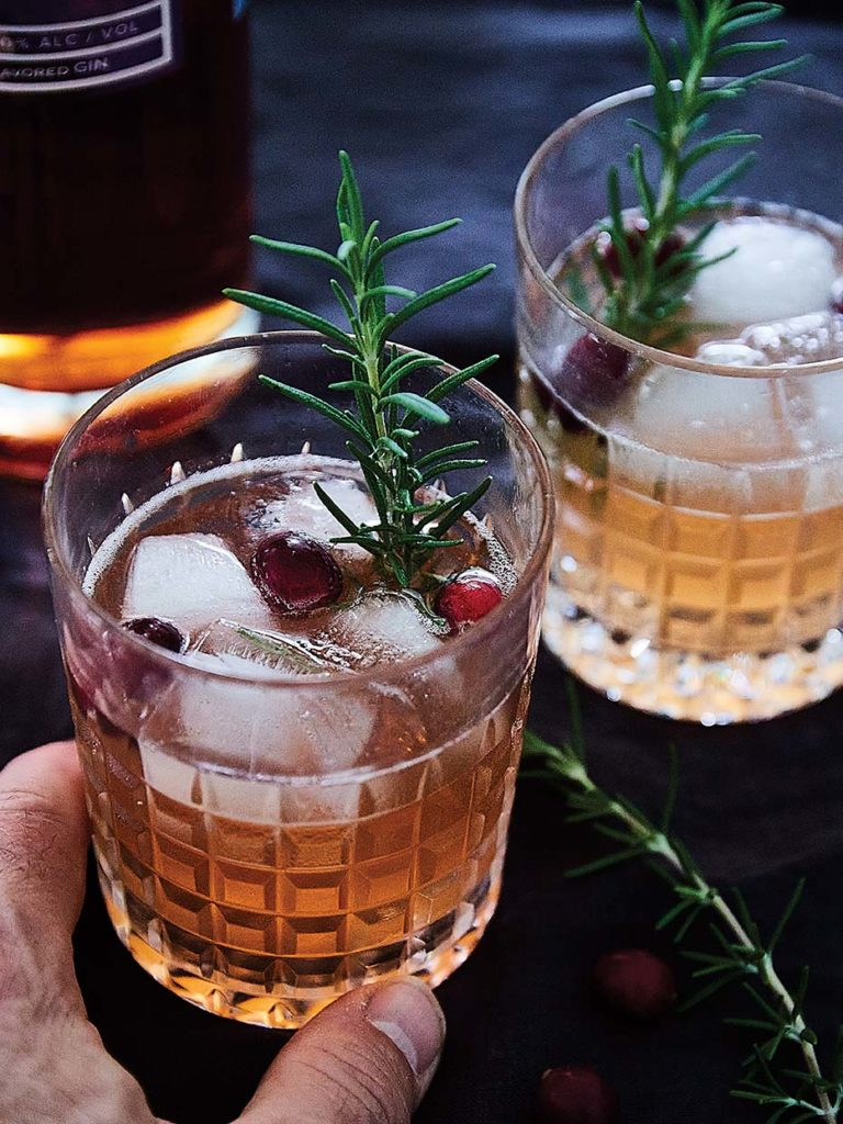 Making cocktails at home with cranberry gin from Sweetgrass Winery and Distillery and ginger ale, garnished with a rosemary sprig and fresh Maine cranberries.